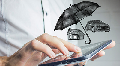 A person using a digital tablet with an umbrella, car and house illustrations above it